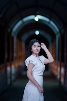 Giovane donna di bellezza in abito bianco di luce notturna
