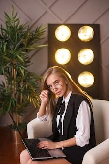 Giovane donna di bellezza in ubicazione di vetro nell'ufficio con il computer portatile.