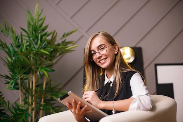 Giovane donna di bellezza in ubicazione di vetro nell'ufficio con la compressa