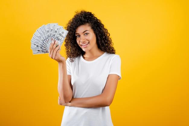 Giovane donna di colore africana con dollari di denaro in mano isolato su giallo