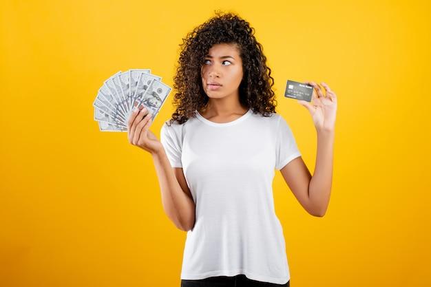 Giovane donna di colore africana con i soldi in dollari e la carta di credito a disposizione isolata sopra giallo