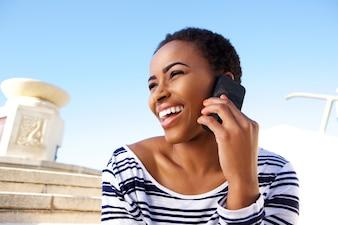Giovane donna di colore allegra che ascolta il telefono cellulare