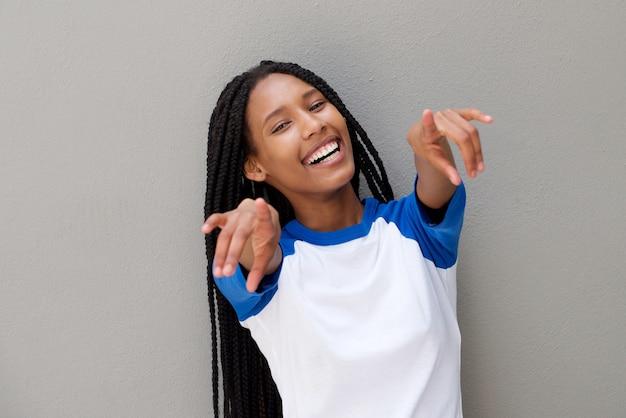 Giovane donna di colore allegra che indica le dita contro fondo grigio