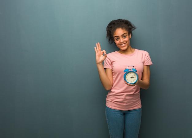 Giovane donna di colore allegra e sicura che fa gesto giusto. ha in mano una sveglia.