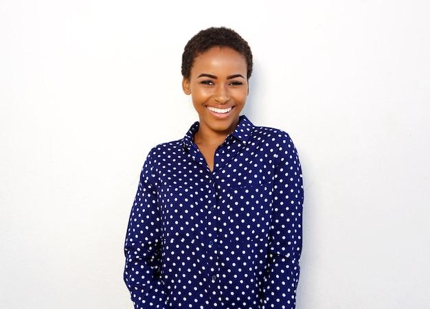 Giovane donna di colore attraente che sorride contro la priorità bassa bianca isolata