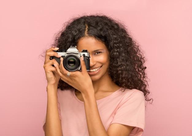 Giovane donna di colore attraente felice con una macchina fotografica d'annata che si concentra sullo spettatore con un sorriso amichevole raggiante sul rosa