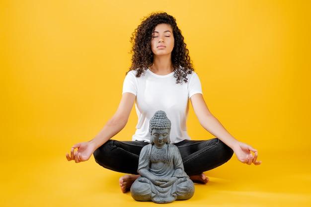 Giovane donna di colore calma che medita e che fa yoga con buddha isolato sopra giallo