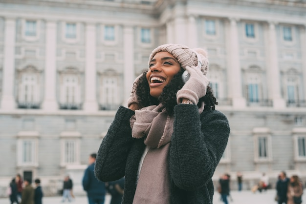Giovane donna di colore che ascolta la musica e che balla sul telefono cellulare vicino al palazzo reale in inverno