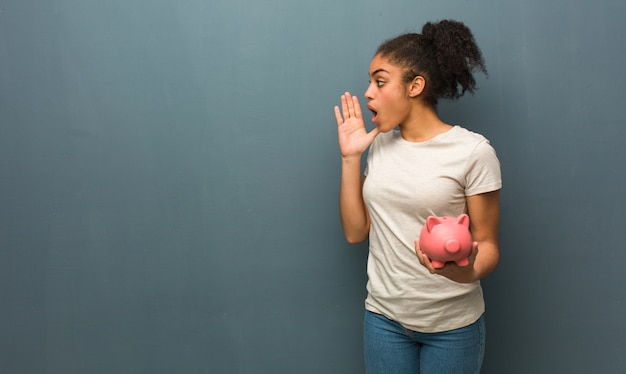 Giovane donna di colore che bisbiglia sottotono di gossip sta tenendo in mano un salvadanaio