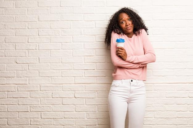 Giovane donna di colore che dubita e che alza le spalle, concetto di indecisione e insicurezza, incerto su qualcosa