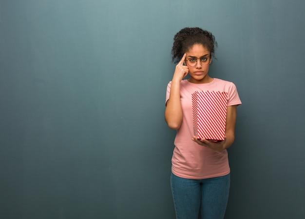 Giovane donna di colore che fa un gesto di concentrazione. lei è in possesso di un secchio di popcorn.