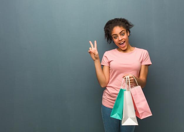 Giovane donna di colore che fa un gesto di vittoria sta tenendo i sacchetti della spesa.