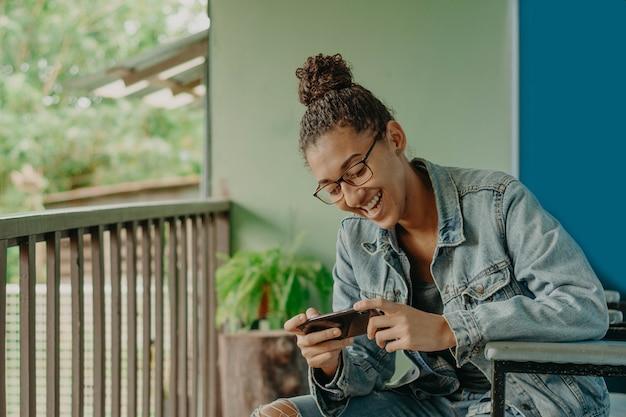 Giovane donna di colore che gioca o che chiacchiera con il suo smartphone.
