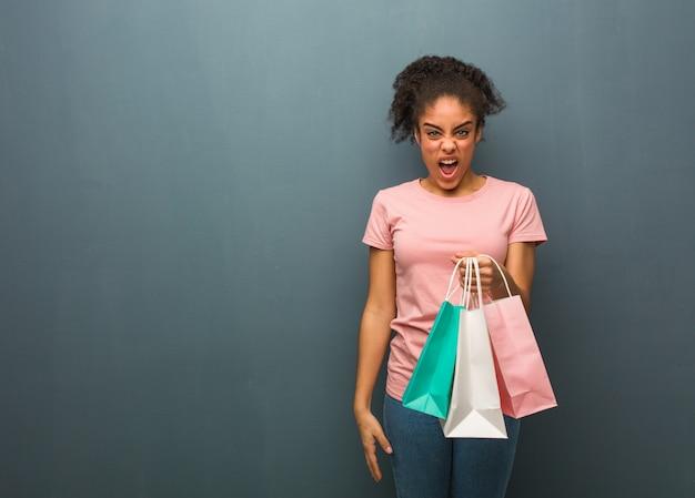 Giovane donna di colore che grida molto arrabbiato ed aggressivo. lei è in possesso di una borsa della spesa.