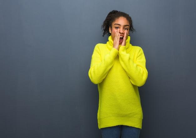 Giovane donna di colore che grida qualcosa di felice davanti