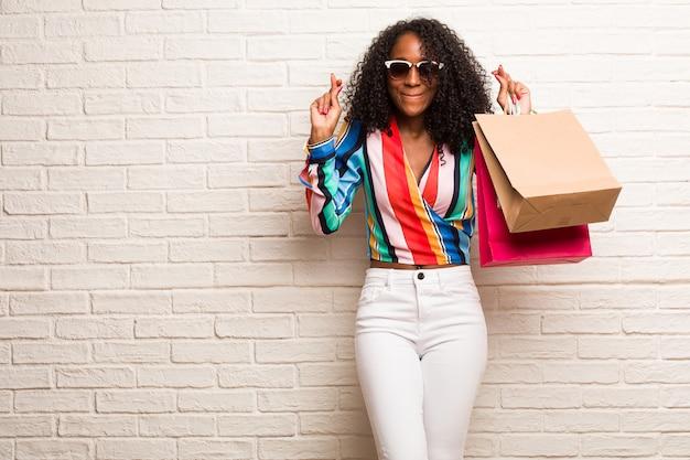 Giovane donna di colore che incrocia le dita, desidera essere fortunato per i progetti futuri