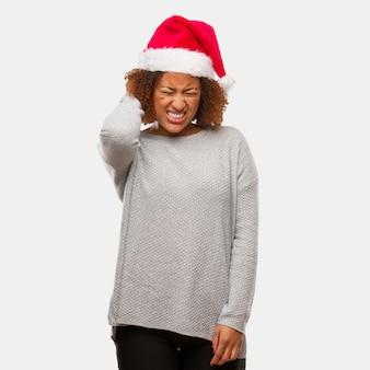 Giovane donna di colore che indossa un dolore al collo sofferenza del cappello di santa