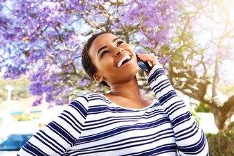Giovane donna di colore che ride con il telefono cellulare all'esterno