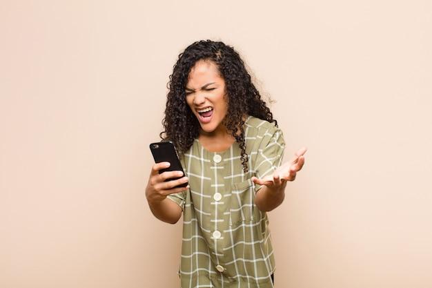 Giovane donna di colore che sembra arrabbiata, infastidita e frustrata che grida wtf o cosa c'è di sbagliato in te con uno smartphone