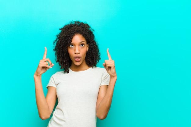 Giovane donna di colore che sembra scioccata, stupita e con la bocca aperta, che punta verso l'alto con entrambe le mani per copiare lo spazio contro la parete blu