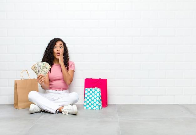 Giovane donna di colore che sembra sorpresa con la bocca aperta e le mani sulle guance che si siedono sulle banconote della tenuta del pavimento