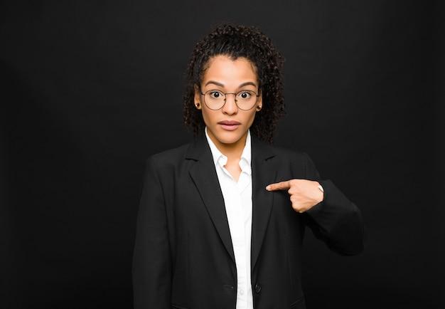 Giovane donna di colore che si sente confusa, perplessa e insicura, indicando se stessa e chiedendosi chi, io? contro il muro nero