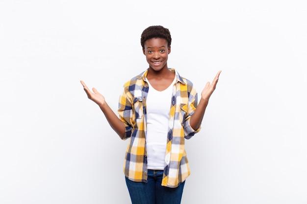 Giovane donna di colore che si sente felice, eccitata, sorpresa o scioccata, sorridente e stupita per qualcosa di incredibile