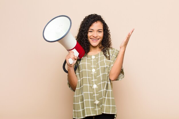 Giovane donna di colore che si sente felice, sorpresa e allegra, sorridente con atteggiamento positivo, realizzando una soluzione o un'idea che tiene un megafono