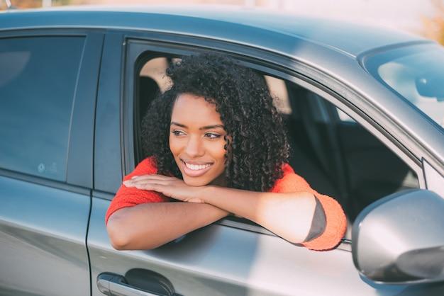 Giovane donna di colore che si siede nel sorridere dell'automobile