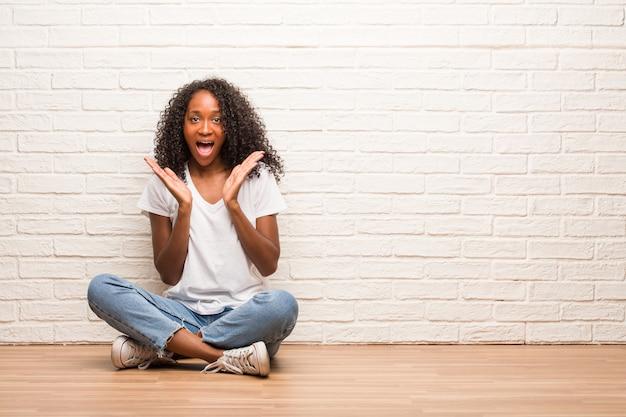 Giovane donna di colore che si siede sul pavimento di legno sorpreso e sconvolto, guardando con gli occhi spalancati