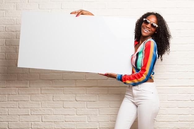 Giovane donna di colore che tiene qualcosa con le mani, mostrando un prodotto, sorridente e allegro, offrendo un oggetto immaginario