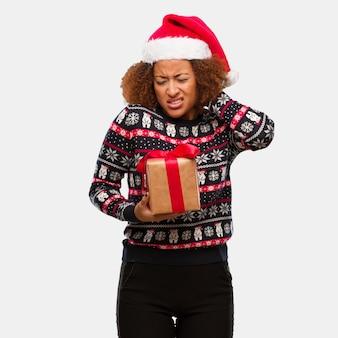 Giovane donna di colore che tiene un regalo nel dolore di collo di sofferenza di giorno di natale