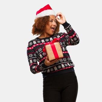 Giovane donna di colore che tiene un regalo nel giorno di natale che fa il gesto di un cannocchiale