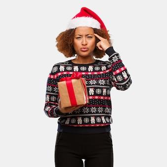 Giovane donna di colore che tiene un regalo nel giorno di natale che fa un gesto di concentrazione