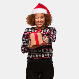 Giovane donna di colore che tiene un regalo nel giorno di natale che raggiunge fuori per accogliere qualcuno