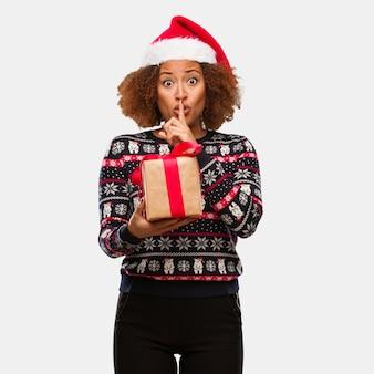 Giovane donna di colore che tiene un regalo nel giorno di natale mantenendo un segreto o chiedendo il silenzio