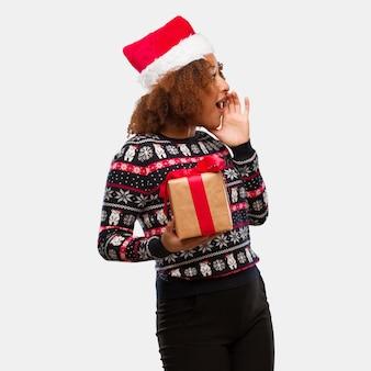 Giovane donna di colore che tiene un regalo nel sottotono di pettegolezzo di sussurro di giorno di natale