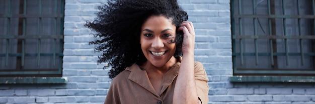 Giovane donna di colore con i capelli afro che ride e che gode