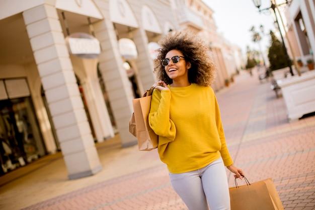 Giovane donna di colore con i capelli ricci nello shopping