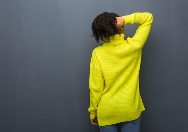 Giovane donna di colore da dietro a pensare a qualcosa