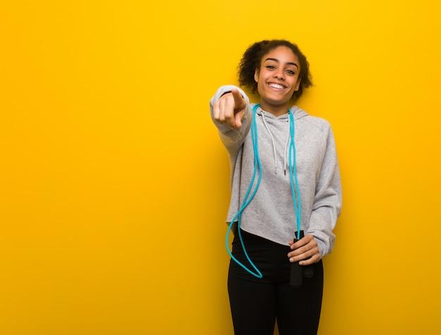 Giovane donna di colore di forma fisica allegra e sorridente. tenendo una corda per saltare.