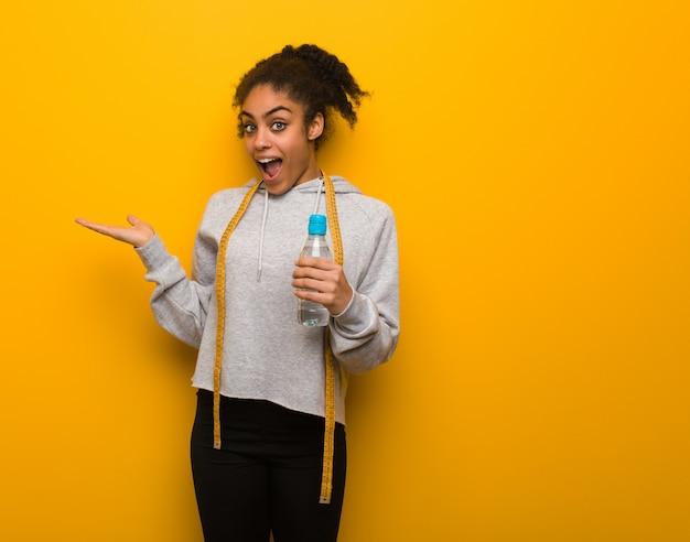 Giovane donna di colore di forma fisica che tiene qualcosa con la mano. holding una bottiglia di acqua.