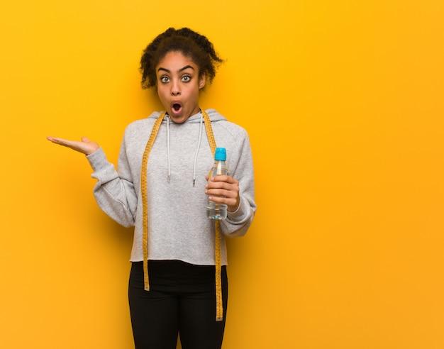 Giovane donna di colore di forma fisica che tiene qualcosa sulla mano della palma. holding una bottiglia di acqua.