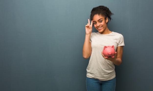 Giovane donna di colore divertente e felice facendo un gesto di vittoria. ha in mano un salvadanaio.
