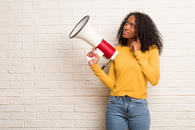 Giovane donna di colore dubita e confusa, pensando a un'idea o preoccupata per qualcosa
