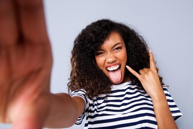 Giovane donna di colore felice che prende selfie contro la parete grigia