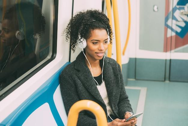 Giovane donna di colore felice che si siede dentro la metropolitana che ascolta la musica