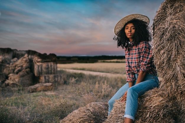 Giovane donna di colore felice che si siede su un mucchio di fieno