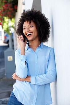 Giovane donna di colore felice che sorride e che parla sul cellulare