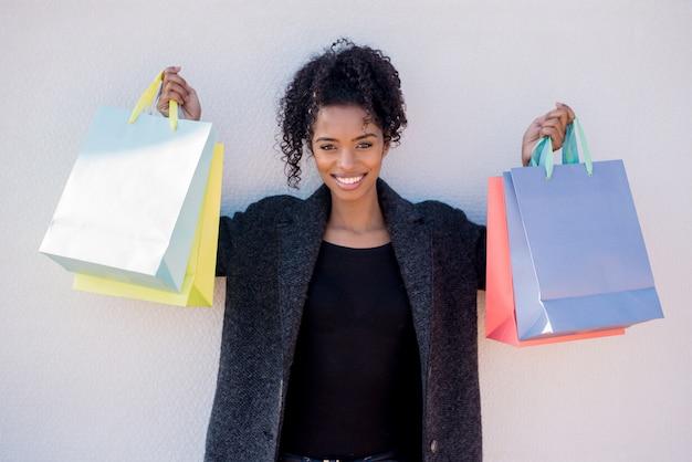 Giovane donna di colore felice con i sacchetti della spesa contro una parete bianca